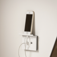 iPhone sitting on a Clipsal wall shelf with a USB outlet and phone charger attached.