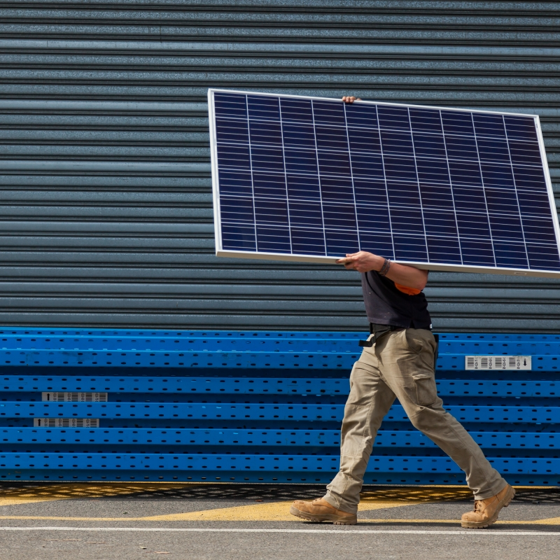 Image of a technician carrying a solar panel
